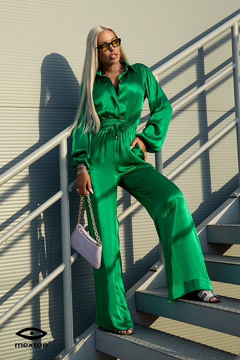 Green satin jumpsuit characterized by fluid and wide trousers and a bodice